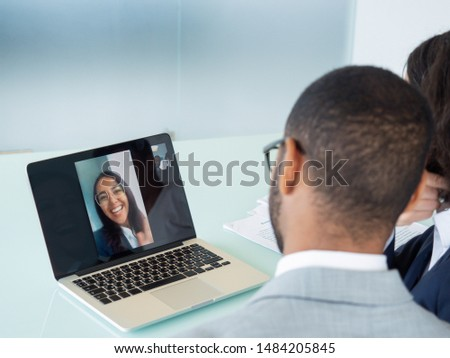 Happy business colleagues chatting through video call. Office employees sitting at laptop, their young female colleague waving hello from screen. Video call concept #1484205845