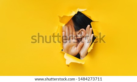 Female ear and hands close-up. Copy space. Torn paper, yellow background. The concept of eavesdropping, espionage, gossip and the yellow press. Royalty-Free Stock Photo #1484273711