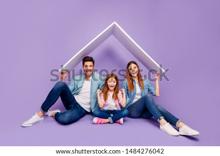 Portrait of three family members sitting floor under new roof wear casual clothes isolated purple background