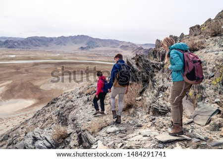 Mongolia Ulgii 2019-05-04 Tourist group go hiking and climbing together with guide, coming down from mountain top. Back view. Concept freedom, backpacker, conquer peak, difficult climb, sport walking #1484291741