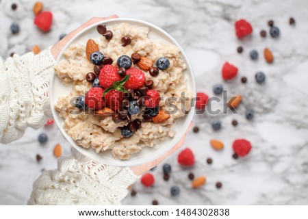Healthy oatmeal served with berries, chocolate chips, almonds and honey. Bowl held in a womans hands over a marble table background. Shot from top view.