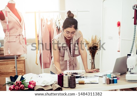 Attractive Asian female fashion designer working in home office workshop. Stylish fashionista woman creating new cloth design collection. Tailor and sewing. People lifestyle and occupation concept #1484311382