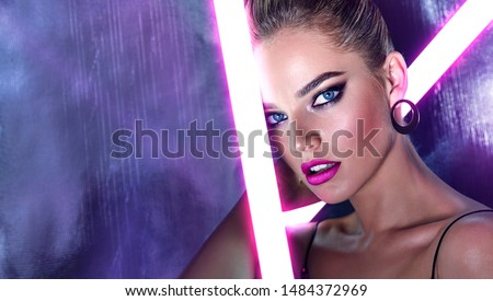 Portrait of a beautiful young tanned girl in big sunglasses in a pink shiny dress in the studio on a silver background with a pink and purple hue. Glowing fluorescent lamps in the face. #1484372969