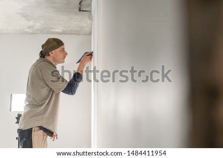 Young repairman aligns with plastic spatula. Worker glueing wallpapers on concrete wall. Repair the apartment. Home renovation concept. White Wallpaper for paint #1484411954