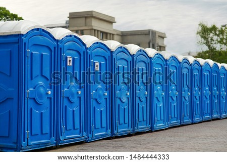 Long row of portable bio toilet cabins in a city street. Line of chemical toilets for the holiday, festival and crowd of people. Blue cabines of bio toilets in the city center. WC. #1484444333