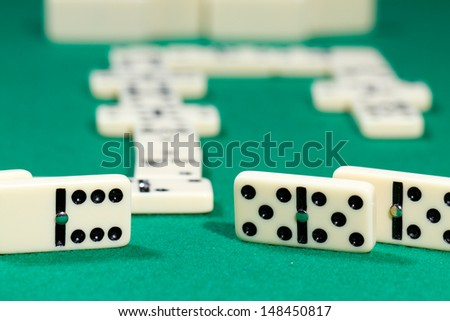 Close up of domino pieces with black dots in green table #148450817