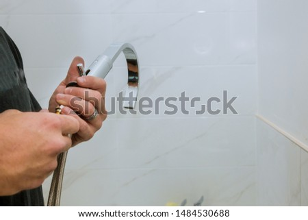Hands plumber at work in a bathroom installation a new faucet for a sink #1484530688