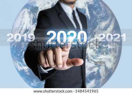 Businessmen are touching the year 2020 and are in transition of the times in the business world. Concept of targeting for success. The Earth element  in the image by NASA (www.nasa.gov) #1484541965