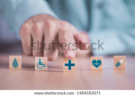 Businessman chooses a emoticon icons healthcare medical symbol on wooden block , Healthcare and medical Insurance concept #1484583071