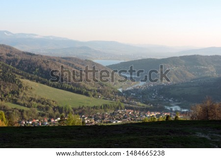 A view of a forest, the Soła river, the Międzybrodzkie lake and a city in the valley in the mountain range of Little Beskids in southern Poland #1484665238