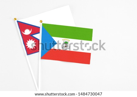 Equatorial Guinea and Nepal stick flags on white background. High quality fabric, miniature national flag. Peaceful global concept.White floor for copy space. #1484730047