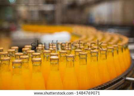 Beverage factory interior. Conveyor flowing with bottles for juice or water. #1484769071