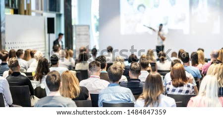 Speaker giving a talk in conference hall at business event. Audience at the conference hall. Business and Entrepreneurship concept. Focus on unrecognizable people in audience. #1484847359