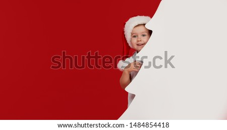 Happy little girl child in Santa hat peeking from behind blank sign banner in the shape of Christmas trees. Isolated on red background. Space for Your Text. Sale, holidays, christmas, new year concept