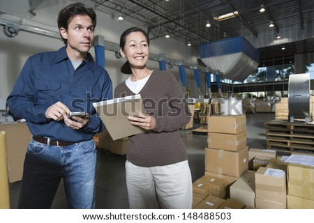 Multiethnic man and woman in distribution warehouse #148488503