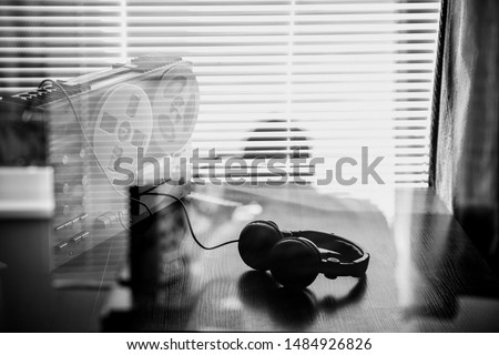 Wiretapping on the reel tape recorder. Headphones near the technique. Special agent work. Retro old school spying on conversations. Black and white photo.