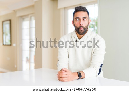 Handsome hispanic man wearing casual white sweater at home making fish face with lips, crazy and comical gesture. Funny expression. #1484974250