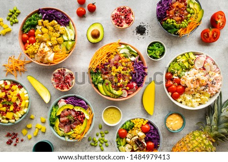 Mix of hawaiiajn Salmon and Tuna poke bowls in colorful bowls with fruits and vegetable around on light background. Top view, overhead, flat lay Royalty-Free Stock Photo #1484979413