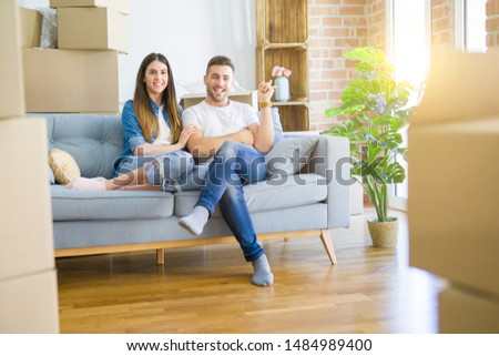 Young beautiful couple relaxing sitting on the sofa around boxes from moving to new house with a big smile on face, pointing with hand and finger to the side looking at the camera. #1484989400
