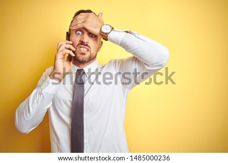 Young handsome business man talking on the phone over yellow isolated background stressed with hand on head, shocked with shame and surprise face, angry and frustrated. Fear and upset for mistake. #1485000236