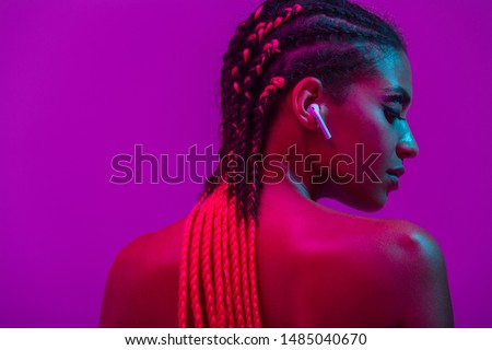 Close up beauty fashion portrait of an attractive young topless african woman wearing dreadlocks standing isolated over purple background, listening to music with earphones #1485040670