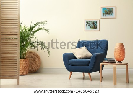 Stylish room interior with comfortable furniture and plant near beige wall #1485045323