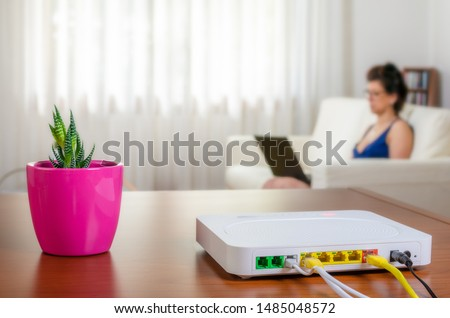 Close up of a modem router on a table in a living room with a woman using a laptop while sitting on the sofa in background #1485048572