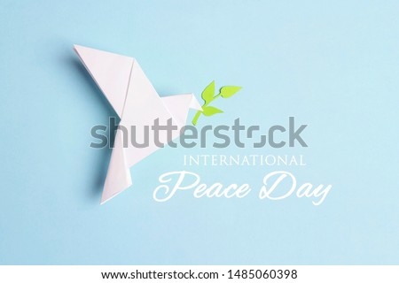 World Peace Day greeting card. Paper origami dove of peace with olive branch and text on a blue background. #1485060398