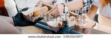 panoramic shot of african american man holding carton plates with hot dogs near customers  #1485065897