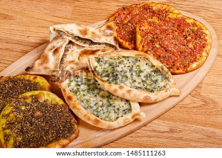 Mix Baked Fatayer and Manakeesh Pastry Styled and Garnished on a Plate #1485111263