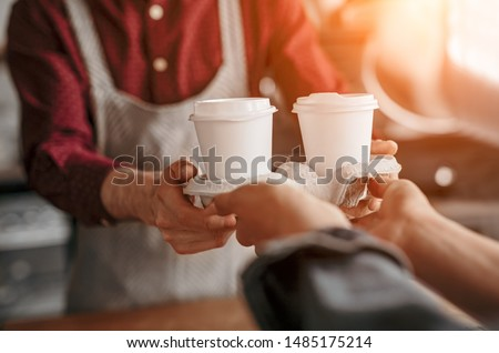 Crop man in apron giving disposable cups of hot coffee in carton holder to customer in bright morning sunrays #1485175214