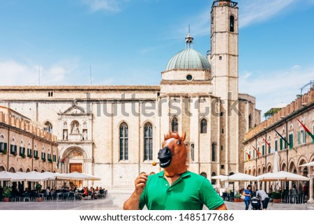 horse man standing in the middle of the historic square of Ascoli Piceno in Italy, eating a fried olive stuffed with pork, named oliva ascolana. It is a famous italian street food. #1485177686