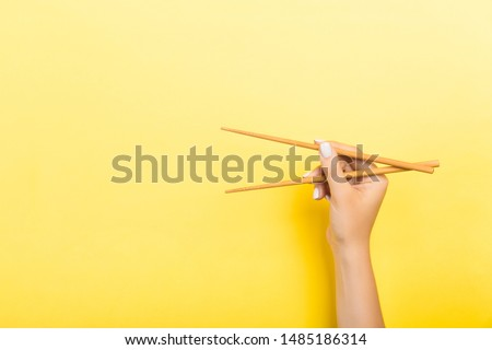 Wooden chopsticks holded with female hands on yellow background. Ready for eating concepts with empty space. #1485186314