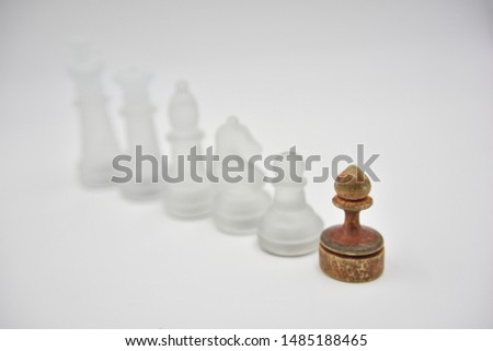 glass chess figures behind wooden ponce on white background #1485188465