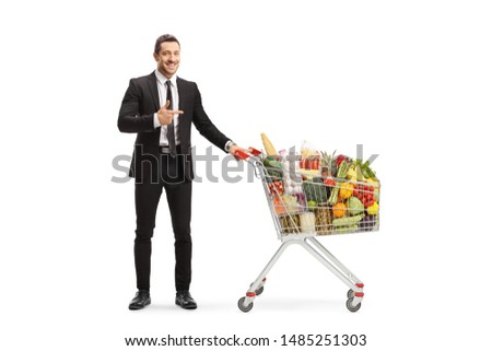 Full length portrait of a young man in a suit standing with a shopping cart full of food and pointing isolated on white background Royalty-Free Stock Photo #1485251303