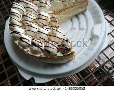 Cake with cream cones sprinkled and nut crumbs on brown mosaic surface. One piece is cut off. Close-up food photo. Сonfectionery. Pastry-shop. Delicious sweet dessert rich in carbohydrates and fat. #1485325052