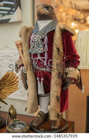 An eagle in a royal mantle in a short fur coat stands on two legs #1485357929