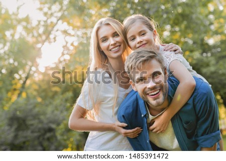 Man carrying his daughter on his back with smiling woman supporting at park while looking on each other #1485391472