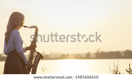 silhouette of a young beautiful girl playing the saxophone at sunrise by the river, a woman in a long dress on the nature at sunrise relaxing, concept music #1485606650