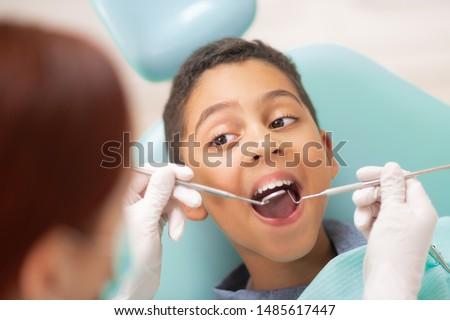 Boy visiting dentist. Handsome dark-skinned boy opening mouth while visiting dentist #1485617447
