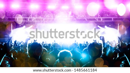Concert spectators in front of a bright stage with live music #1485661184