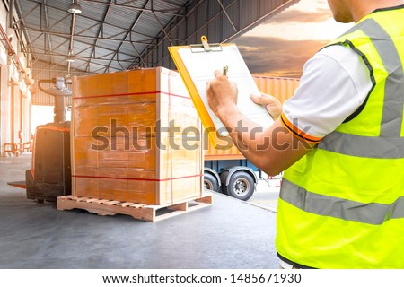 Worker courier holding clipboard writing on checklist load shipment into a truck. Freight industry warehouse logistics and transport.  Electric forklift pallet jack with large shipment pallet goods. #1485671930
