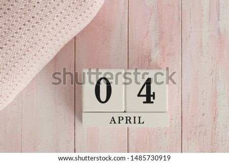 4 April Date on Cubes. Date on painted pink wood, next to baby blanket. Theme of baby due dates and birth dates. #1485730919