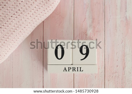 9 April Date on Cubes. Date on painted pink wood, next to baby blanket. Theme of baby due dates and birth dates. #1485730928