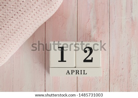 12 April Date on Cubes. Date on painted pink wood, next to baby blanket. Theme of baby due dates and birth dates. #1485731003