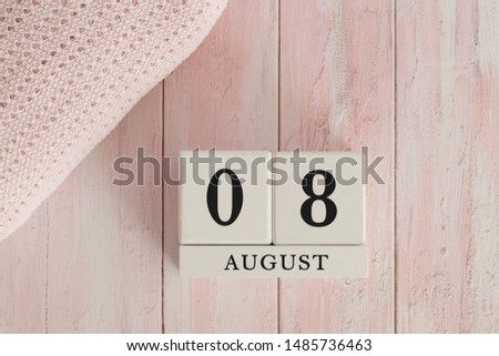 8 August Date on Cubes. Date on painted pink wood, next to baby blanket. Theme of baby due dates and birth dates. #1485736463