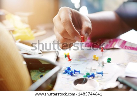 Hand of young man holding push pin holding marking location on map at home office, date planning for travel ,meeting or appointment, deadline, travel planning or holiday concept                        #1485744641