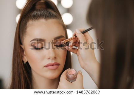 Makeup artist applies eye shadow, perfect evening makeup. Beauty redhead girl with perfect skin and freckles #1485762089