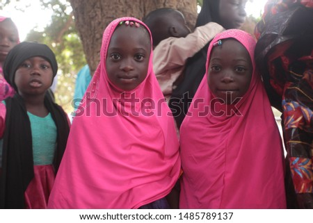 Sukuta, Gambia, Africa, June 4, 2019, close up photography - portrait of a two small african girls with a pink head wrapper, standing outdoors on a sunny summer day by big trees #1485789137