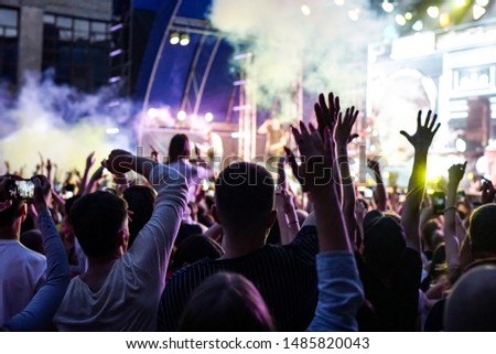 Concert crowd attending a concert, people silhouettes are visible, backlit by stage lights. Raised hands and smart phones are visible here and there. #1485820043